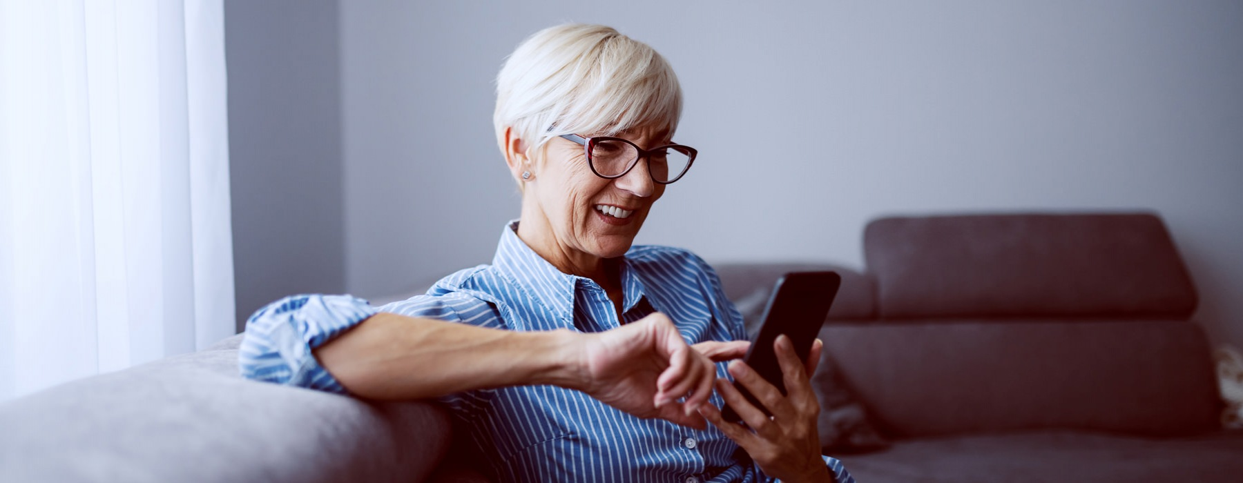 Older woman sitting on a sofa scrolling through her cell phone